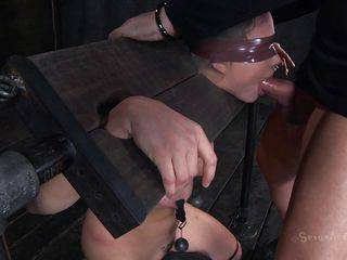 Clamps with weights were attached on her large billibongs and duct tape was used to blindfold her. Now this babe stays there in that bondage device and has a rodeo sex machine underneath her that's rubbing her shaved pussy. To make things interesting an executor comes and deeply mouth bonks this slut girl, chocking her with cock