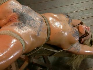 Blonde slut Cameron is all tied up with strings to a wooden table and face hole gagged. With her legs spread, she receives fingered and has a sex tool on her clitoris. Let`s take a close look at that hot oiled up body and with wax all over her! Will her mistress make that whore cum if her cunt receives fisted so hard?