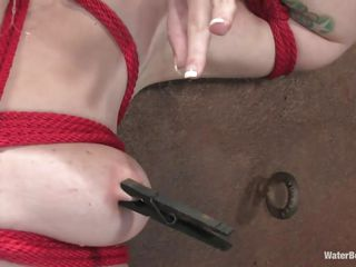 A beautiful white milf with red delicious lips is tied with a red rope and that babe groans and screams because her executor putted that rope between her pussy lips and at the end, a enormous bucket pulls the rope making it enter deeper in that shaved wet cunt. She is tortured and wet, surely now that babe deserves a hard fuck, doesn't she?