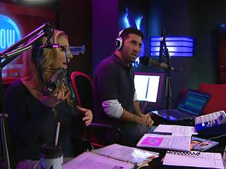 The hosts of Playboy Radio's Morning Show are looking at their guest model who is wearing the dress she'll be wearing to the Playboy Mansion for Halloween. Her head and love melons are overspread in fake fruit like oranges, limes, lemons, and more. She flashes her breasts for the hosts and viewers.