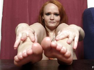 This woman really wants to wrap her feet around a cock and make it cum, but unfortunately she does not have a cock handily available. Therefore, she is making use of the next best thing, which is a nasty big dark dildo standing up right on the table. That babe is caressing that with her feet.
