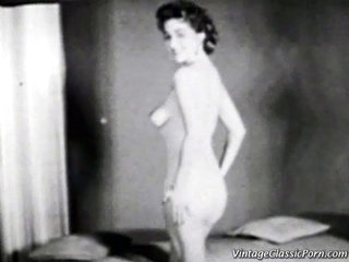 In the 1st scene of this vintage black and white video we see a young woman posing undressed in front of the camera. She stands up at 1st and then kneels down on the floor. In the next scene a undressed gal sits in front of a fire reading a book.