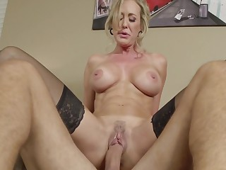 A blonde milf with large tits and a fit tummy is getting fucked