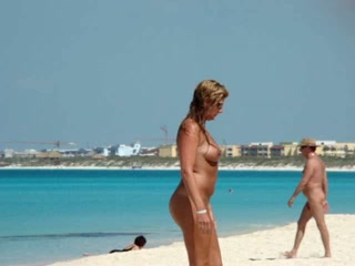 Golden-haired with great body filmed coming out of the sea and walking along the beach naked