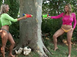 The two busty blonde babes Jannete & Carol went outside for playing in the hot weather & got one another's T-shirts wet with squirt-guns. During their little lesbo game their pussies got wet also, so they had to get totally undressed to show one anoth