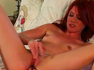 Redhead hottie Elle Alexandra enjoys stimualting her warm clit with her favorite dildo