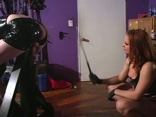 Redhead mistress dominates a lady's man in latex costume