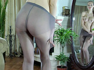 Leggy honey posing topless by the mirror in constricted fitting gray hose